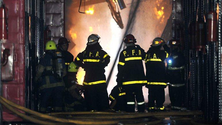 Efectivos de bomberos intentan sofocar el incendio.