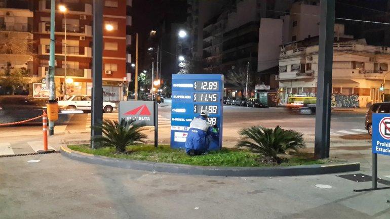 Empleado cambia los precios en una estación de servicio porteña.
