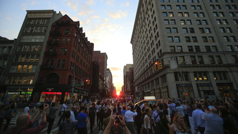 La gente toma fotos al atardecer, durante la ocurrencia Manhattanhenge bi-anual en Nueva York