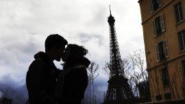 Una pareja se besa frente a la Torre Eiffel en París, Francia