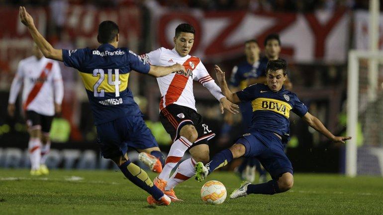 Adrian Cubas y Guillermo Burdisso le disputan la pelota a Sebastian Driussi