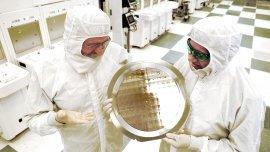 Científicos de IBM sostienen un wafer con los nuevos procesadores desarrollados en 7 nm