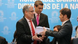 Axel Kicillof le entrega las bases del Presupuesto 2016 al diputado Roberto Feletti.