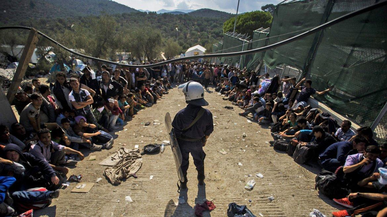 Un policía griego mantiene el orden mientras un grupo de inmigrantes esperan para ser registrados en un campamento para refugiados, ubicado cerca a Moria, en la isla de Lesbos, Grecia