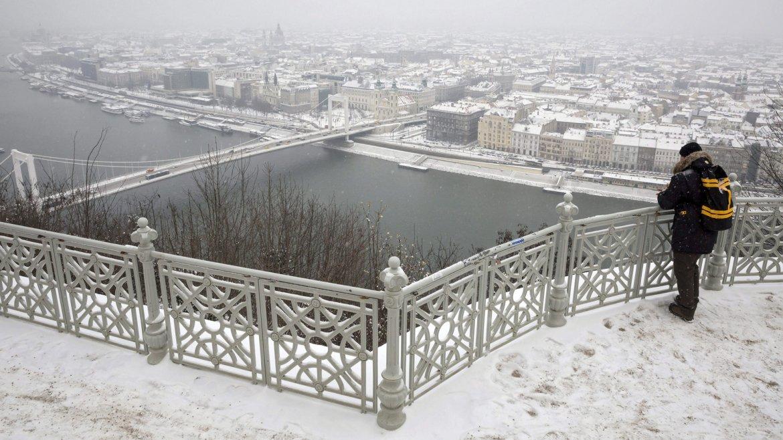 Un hombre observa la ciudad nevada desde el alto de Gellert, en Budapest, Hungría