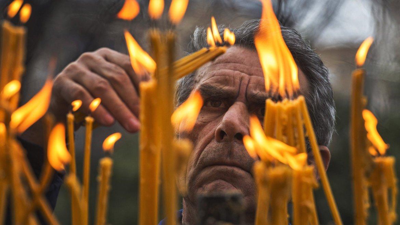 Un creyente ortodoxo enciende velas al finalizar la misa de Navidad en la iglesia de San Clemente en Skopje, antigua república yugoslava de Macedonia