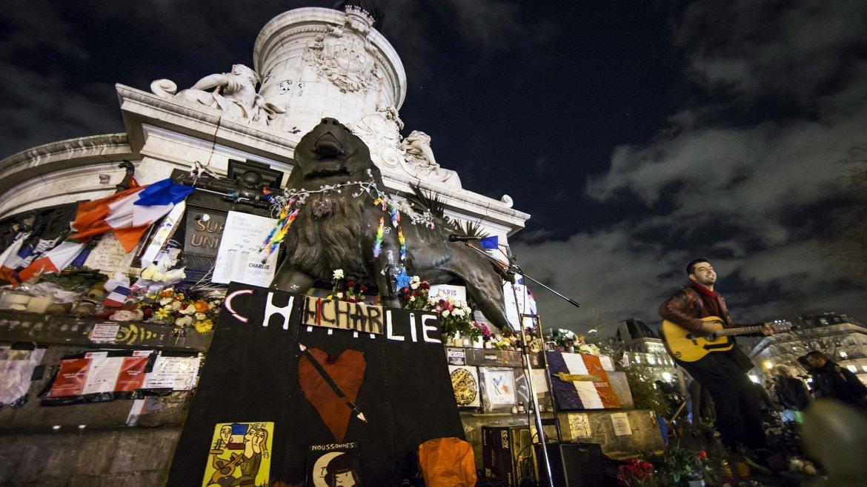 Un músico toca la guitarra durante un evento organizado en la plaza de la República de París, Francia, en homenaje a las víctimas del atentado en la sede la revista satírica Charlie Hebdo