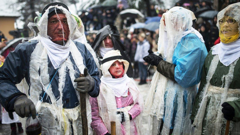 Ciudadanos macedonios disfrazados participan en el carnaval de Vevcani