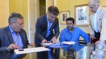 Fernando De Andreis firmando el contrato junto a Luis Segura y Daniel Angelici