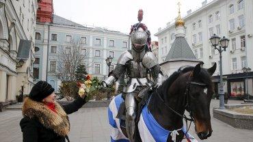 Un caballero con armadura le regala a su amor unas flores por San Valentín en Moscú.