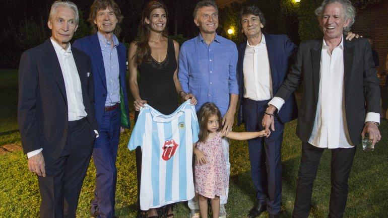 Mauricio Macri sonríe y Juliana Awada sostiene una camiseta de Argentina que lleva impresa la lengua de los Rolling Stones, mientras Keith Richards toma de la mano a Antonia, hija del matrimonio presidencial