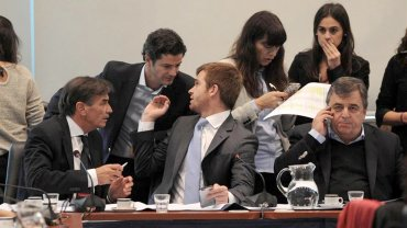 Nicolás Massot dialoga con Luciano Laspina en una reunión de comisión; a su lado, Mario Negri habla por teléfono