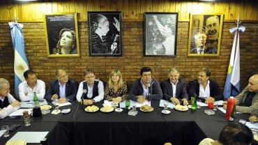 Fernando Espinoza encabeza la reunión del PJ bonaerense, en la noche del lunes, con Cristina, Evita, Juan Perón y Néstor Kirchner a sus espaldas.