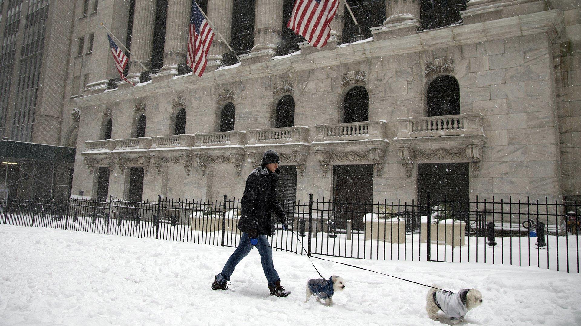 Un hombre pasea a su perro frente a la bolsa de valores de Nueva York