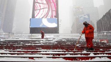 Los empleados de limpieza quitan la nieve de la escalera de Times Square