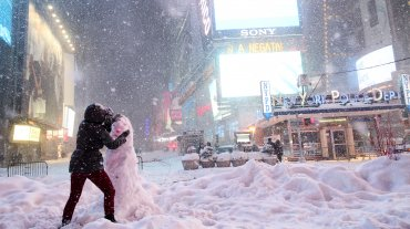 Algunos turistas se atreven a salir a la calle y hacen muñecos de nieve