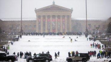La gente aprovecha los escalones del Museo de Arte de Filadelfia llenos de nieve acumulada para tirarse en trineos