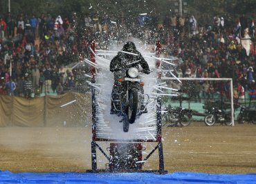 Un policía realiza una acrobacia en su moto durante el desfile del Día de la República en Jammu, India
