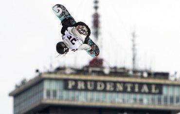 Un participante realiza un salto con la torre Prudential detrás en la competencia de snowboard Fenwey Big Air, en Fenway Park, Boston, Massachusetts