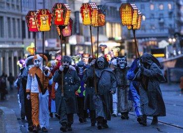 Varios participantes adornados con lamparillas desfilan por las calles al tono de una melodía durante el carnaval de Basilea, Suiza