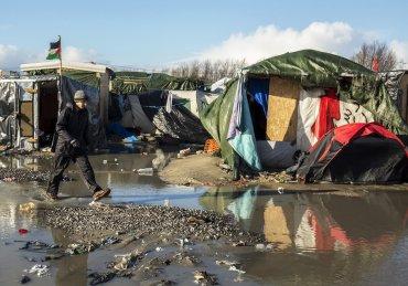 Un refugiado camina por el campamento llamado La Jungla, montado cerca de una zona vallada con contenedores utilizados como alojamientos, en Calais, Francia