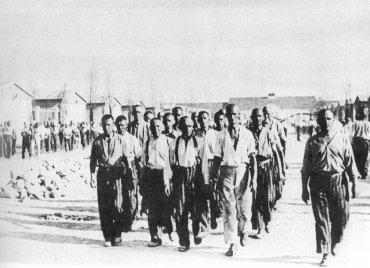 Imagen propagandística tomada el 28 de junio de 1938 de un grupo de reclusos recorriendo la vía principal del campo de concentración Dachau