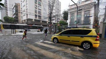 Transeúntes intentan cruzar por una calle inundada debido a las fuertes lluvias producidas por la llegada de un frente frío en el barrio Botafogo, en la zona sur de Río de Janeiro