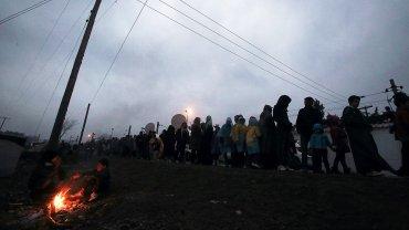 Refugiados alojados en el campamento de Idomeni (Grecia), esperan para pasar la línea del tren y cruzar la frontera con la República de Macedonia