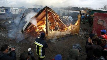 Vista general de un refugio en llamas durante los trabajos de demolición en el campamento conocido como La Jungla, en Calais, Francia