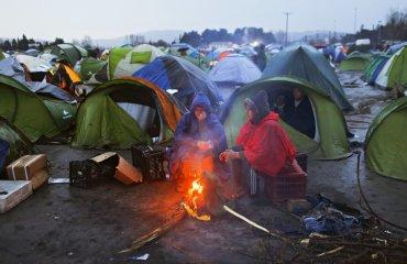 Varios refugiados se calientan junto al fuego entre sus tiendas de campaña en un campamento de refugiados en la frontera entre Grecia y Macedonia
