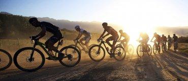 El pelotón de ciclistas avanza con el sol del amanecer como telón de fondo durante la primera etapa de la Absa Cape Epic, en Saronsberg, Ciudad del Cabo, Sudáfrica